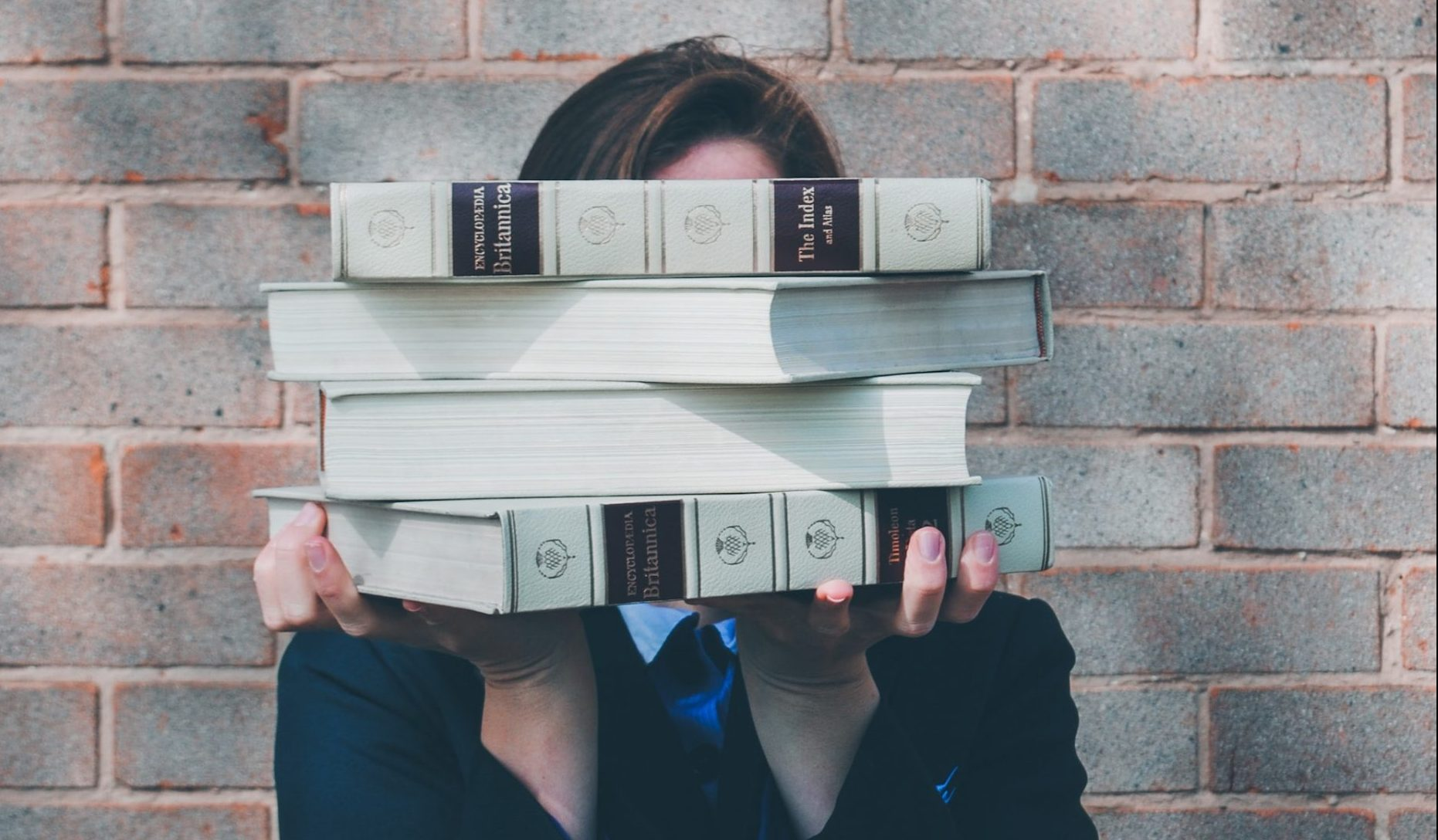 person with a stack of books held over their face